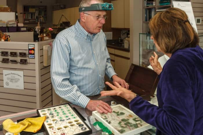 A jeweler appaises some jewelry for a customer.