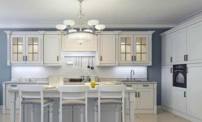 white and gray kitchen with chandelier and under cabinet lighting