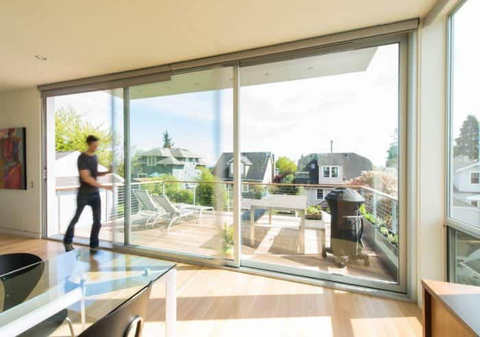 Man Opens Large Sliding Patio Door Between Balcony And Dining Area