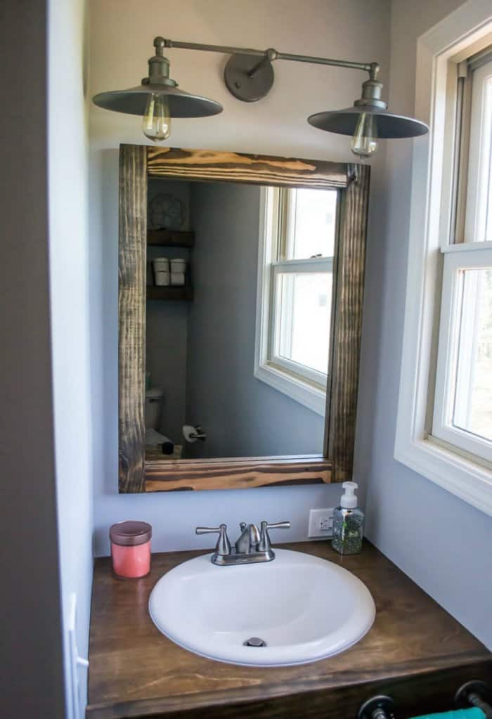 edison bulbs in this fixture match the industrial vibe of the bathroom