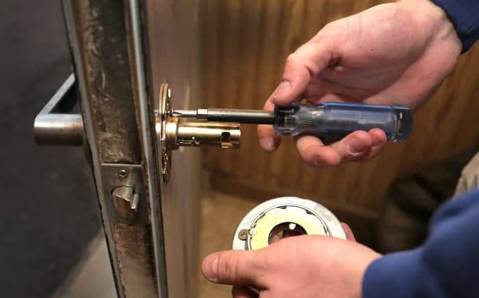 locksmith using tool to fix lock on door