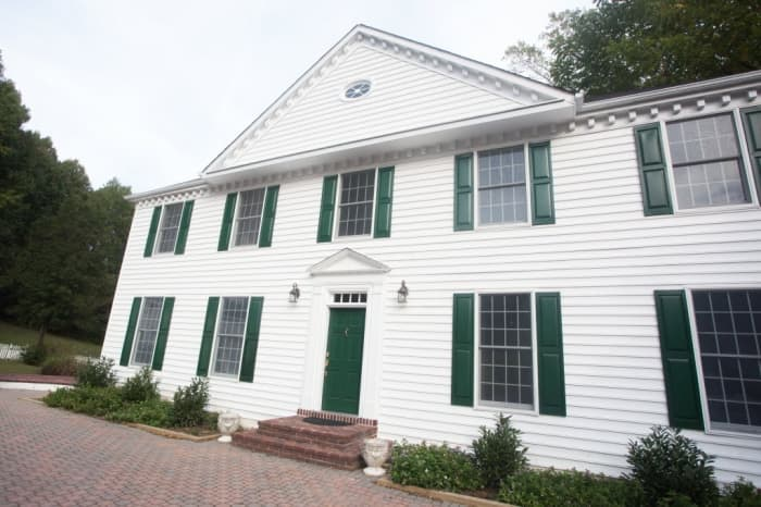 2-story home painted white with green shutters