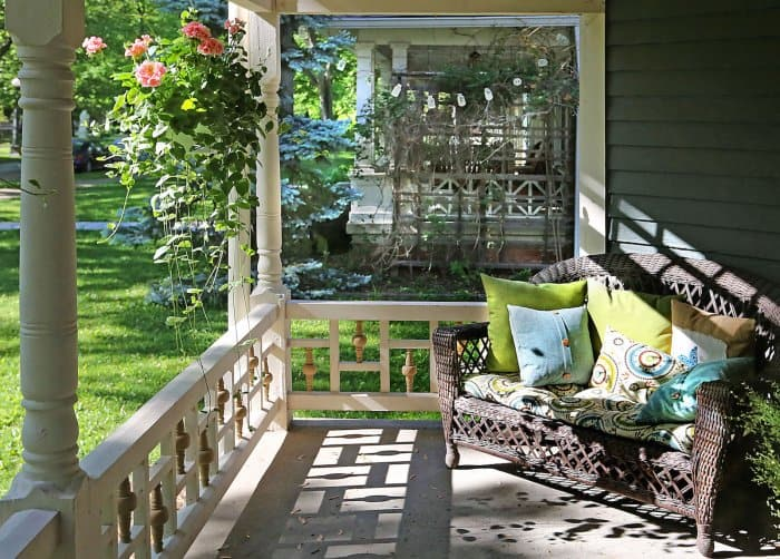 front porch with love seat and hanging flowers