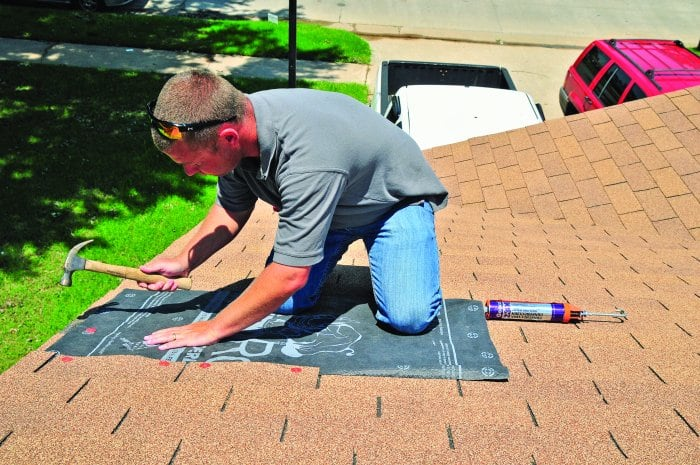 roofer repairing shingles (Photo by Nick Oxford)