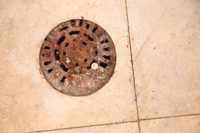 A view of a dirty sewer drain in a basement & What To Do If You Smell Sewer Gas In Your Home | Angieu0027s List