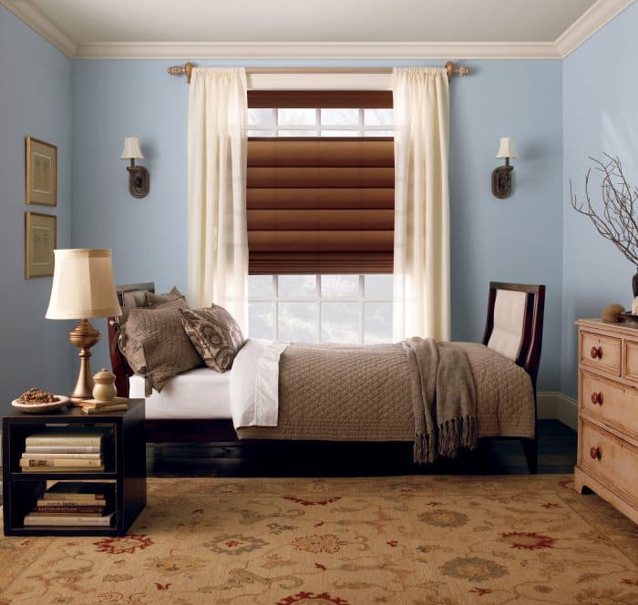 roman shades layered with drapery in bedroom