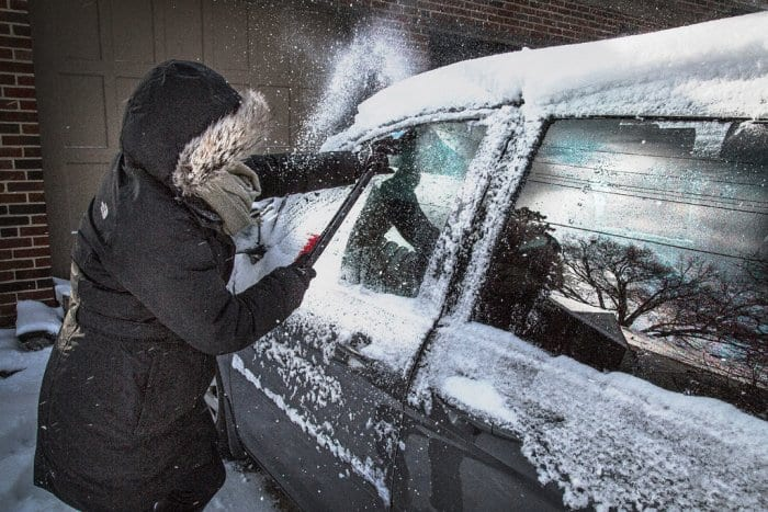 A driver scrapes ice from their car