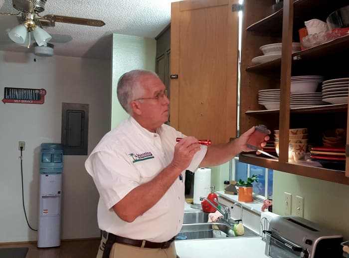 man holding flashlight and inspecting kitchen cabinet