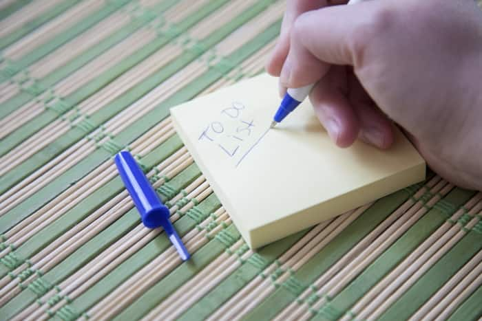 writing to-do list on sticky note