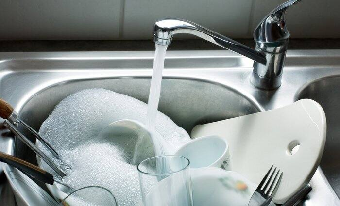 sink full of soapy dishes with water running from faucet