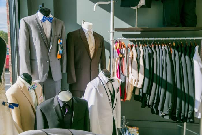 mens suits and tuxedos hanging on rack