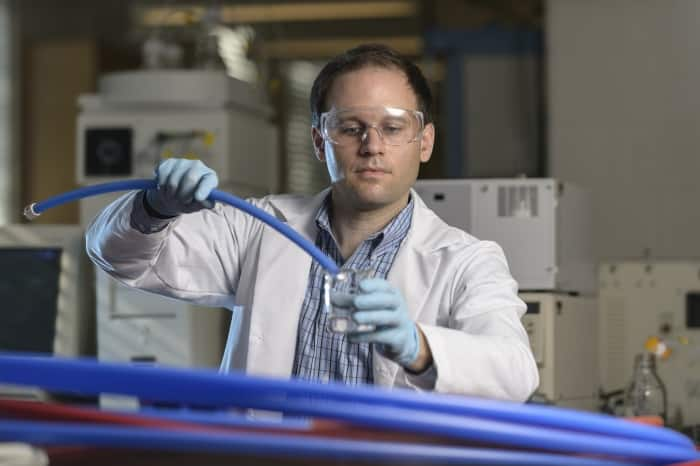 Lab researcher holding plastic pipe in water