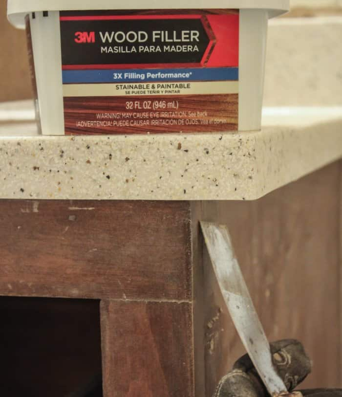 fixing bathroom cabinet with wood putty