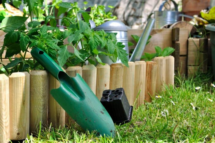 Add a unique garden edge fence with unfinished wood. (Photo courtesy of iStock Photos/Getty Images)