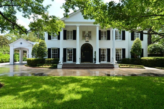 Greek Revival Home With White Exterior, Black Shutters And Landscaped Front  Yard