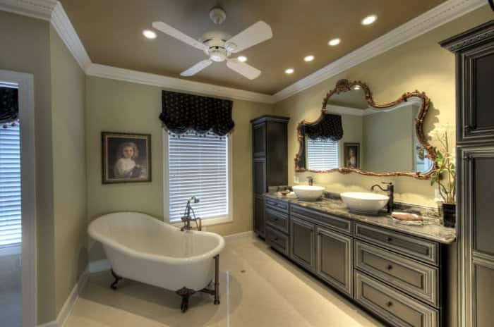 Bathroom with stand-alone tub and large vanity mirror with recessed lighting