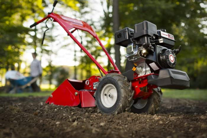 Red Troy-Bilt rototiller on freshly tilled soil.