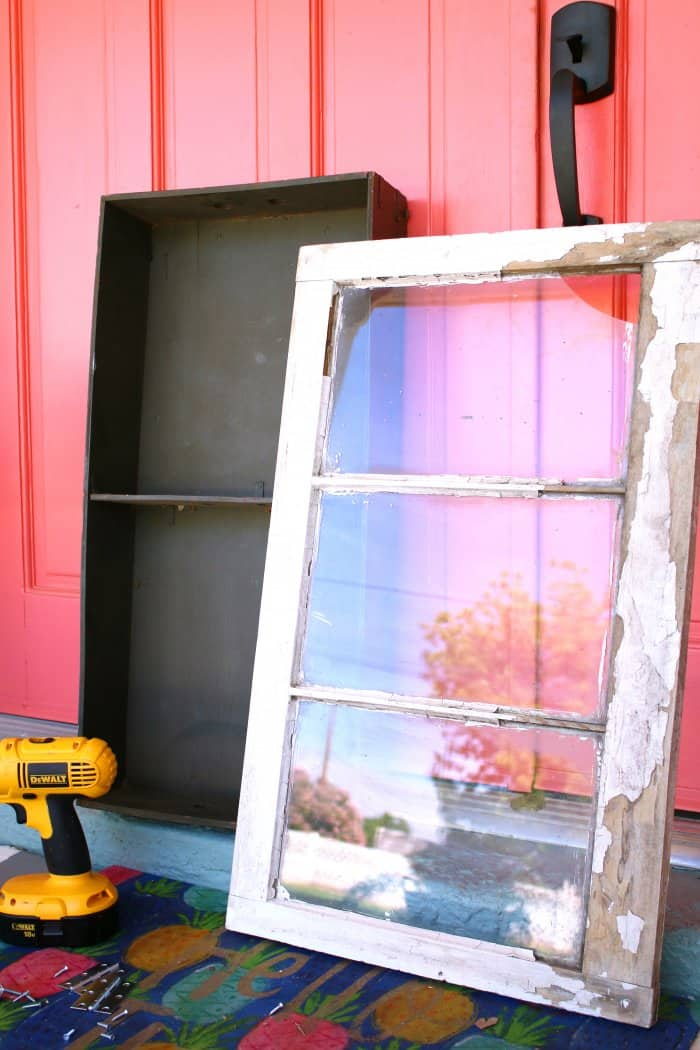 An antique trunk and a chipped vintage window make the perfect cabinet. (Photo courtesy of Lolly Jane)