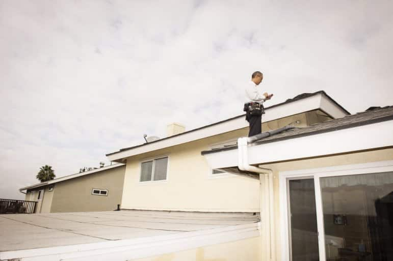 man inspecting a roof