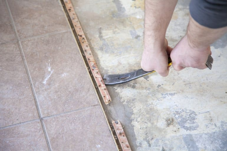 A man uses a pry bar to remove tack strip from a floor.