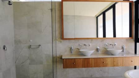A modern looking bathroom scene with two bowl sinks on a wood-faced shelf counter.