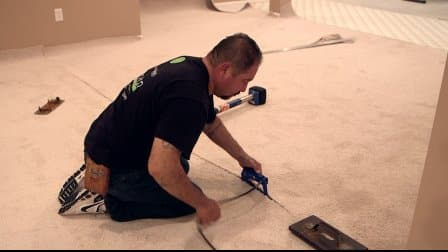 man installs carpet