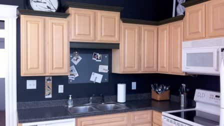 Kitchen with Wood Cabinets and Dark Countertop and Backsplash