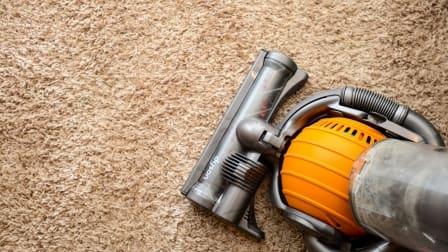 dyson vacuum cleaner on tan, shag carpet