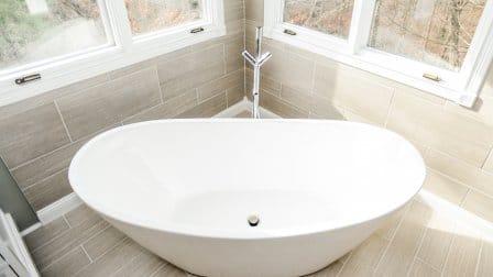 White Ceramic Bathtub In Corner Of Bathroom With Windows Above