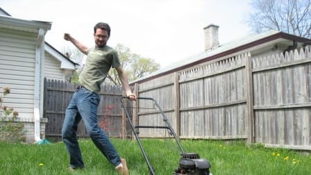 A man starting a push lawnmower