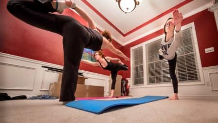 Three women doing yoga in a former dining room space