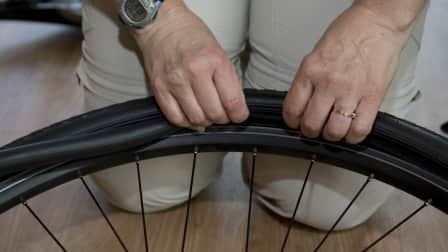 hands replacing the tube in a bicycle tire