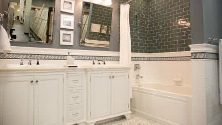 white double vanity and bathtub with subway tile surround