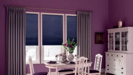 Contemporary dining room with grey-ish purple drapes, bluish purple cellular shades, purple walls and white furnishings