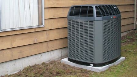 gray heat pump on concrete block