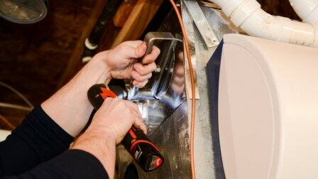 HVAC technician drilling a unit