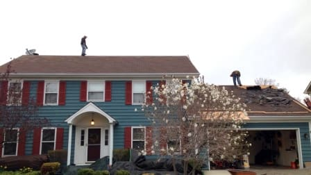 roofers on top of roof tearing off old roof shingles
