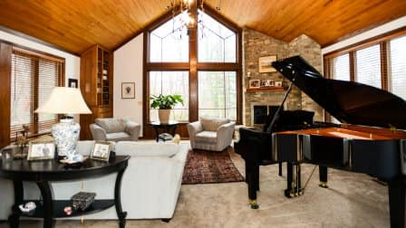 A large family room with a stone fireplace and baby grand piano
