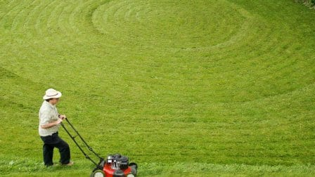 A man mowing in a circular pattern