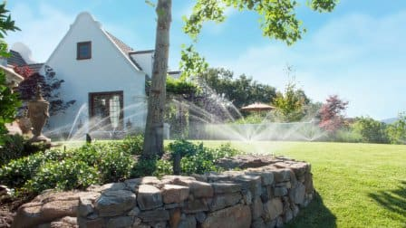 Large yard with multiple sprinklers and a rock ledge with a tree