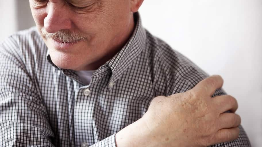 A man grimaces in pain as he grasps his shoulder