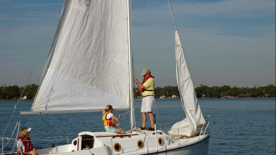 three people on sailboat in open water