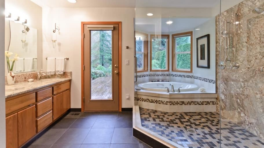 bathroom with large tiled walk in shower and soaking tub