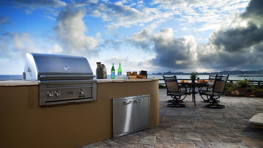 stucco finish open outdoor kitchen on stone patio on near water