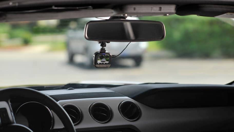 Lifestyle shot of a Cobra CDR 855 BT dash cam, mounted and in use while driving.