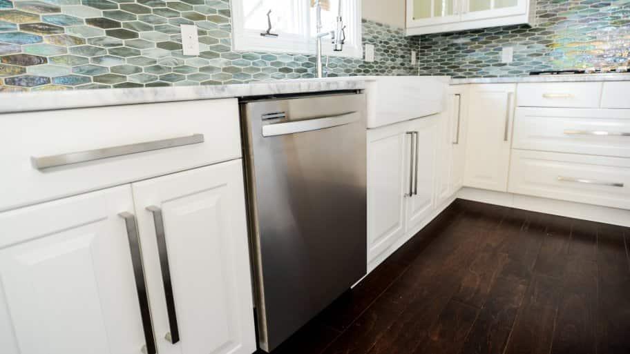Built-in stainless steel dishwasher, white cabinets, tile backsplash.