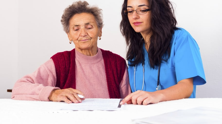 Elderly woman filling out paperwork with younger brunette nurse