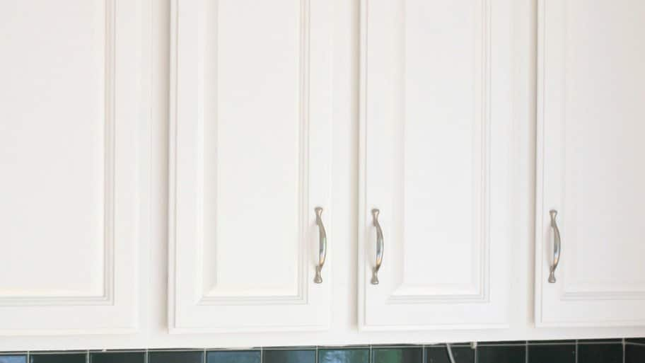 white painted kitchen cabinets with tiny spindles on molding