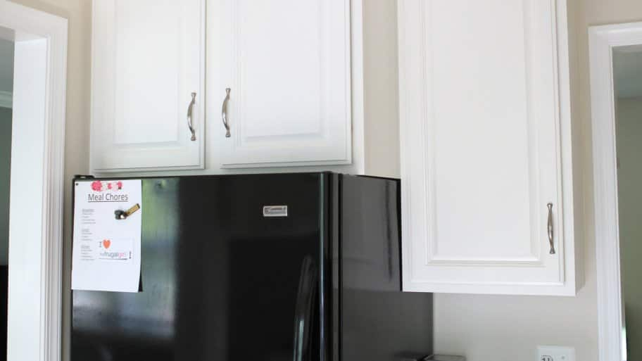 white painted kitchen cabinets above black refrigerator
