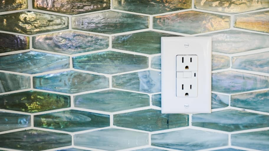 GFCI outlet on a glass tile wall